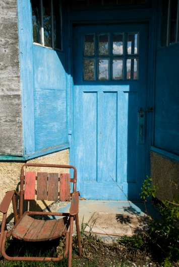 rusted chair in front of bright blue door