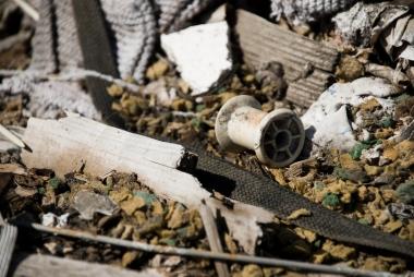 an old thread spool amongst debris