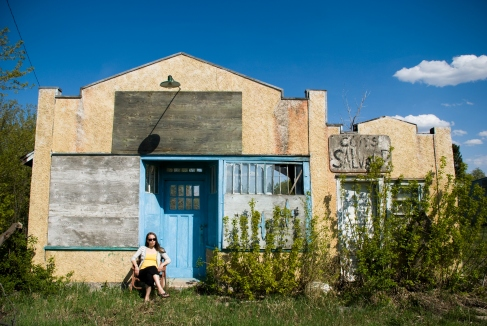 person sitting in front of an abandoned building