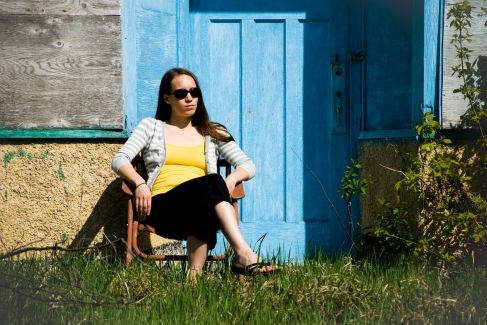 person sitting on a rusted chair by a blue door