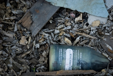 old bottle of methyl hydrate poison in a pile of brown leaves