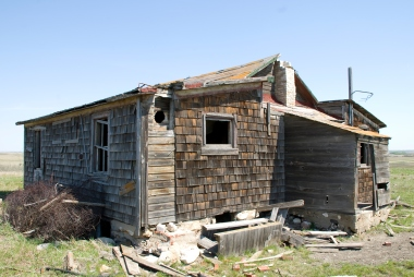 collapsing house with wood siding