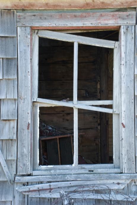 misshapen window looking into an abandoned house