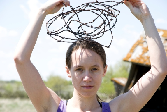 person holding barbed wire above head