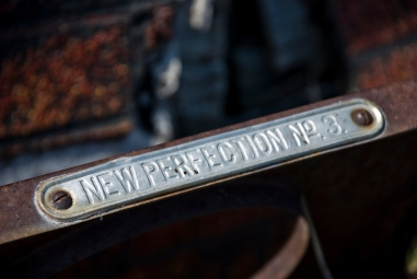close-up of rusted old wood stove, label says New Perfection No 3