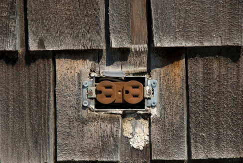 rusted electrical plug on old wooden siding
