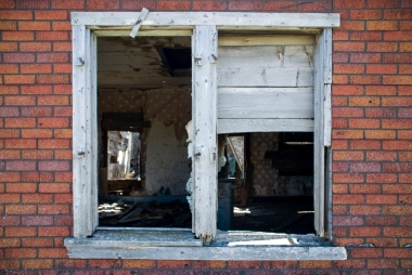 glassless windows looking into an abandoned house