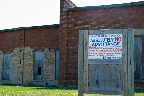 sign next to old brick building - to aid in disease prevention absolutely no admittance
