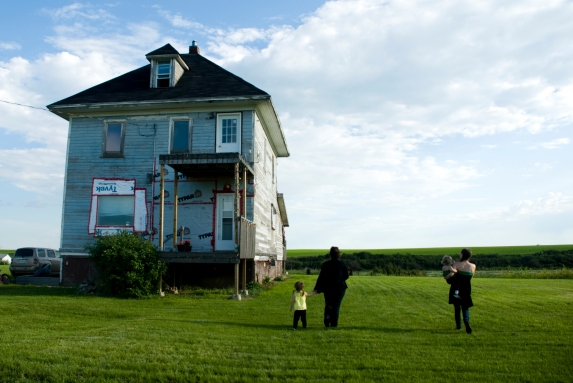 people standing next to an old house under renovation