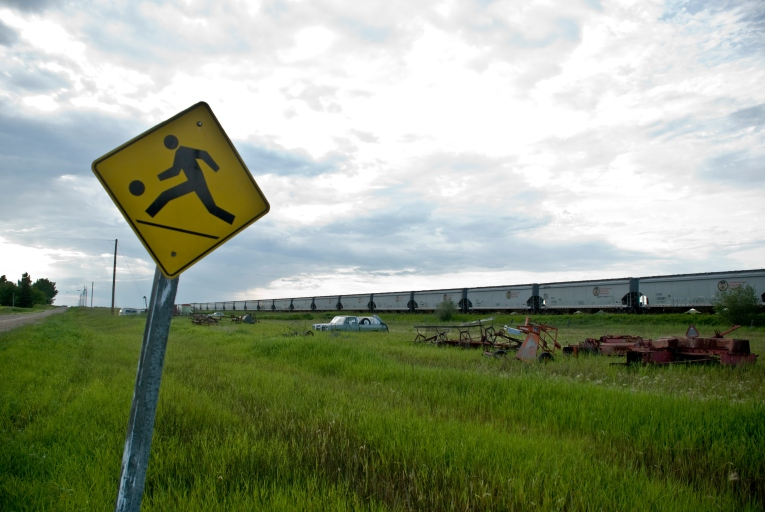 a yellow sign next to old cars and farm machinery