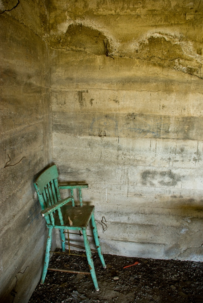 old high chair in a concrete room