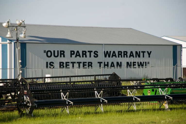 side of building, painted sign says - our parts warranty is better than new