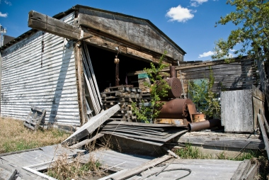 rear of abandoned building, piles of wood and rusted metal