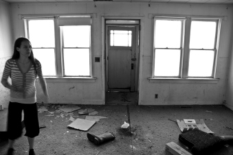 person standing in messy room of abandoned house