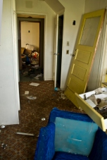 upturned furniture, broken door, abandoned house