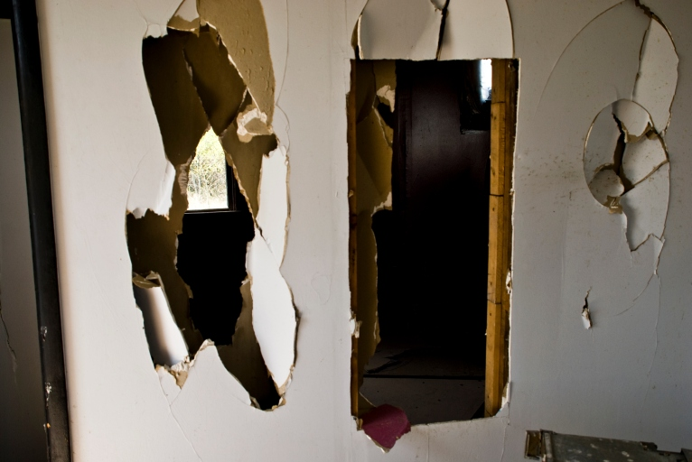 holes through wall in abandoned house