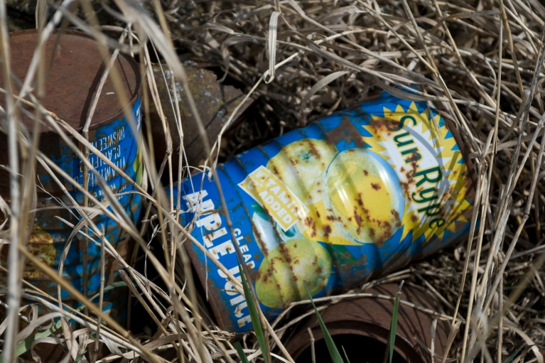 rusted old sun-rype apple juice cans