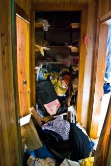 overflowing closet of discarded items in abandoned building