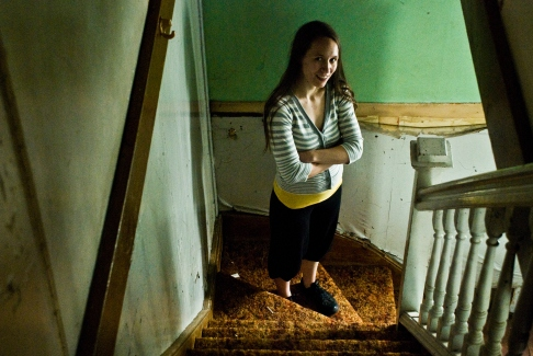 person standing down stairs in abandoned building