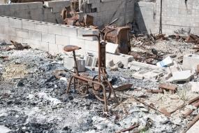 rusted exercise bike amongst burnt debris