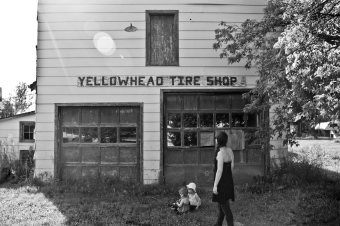adult and children in front of abandoned tire shop