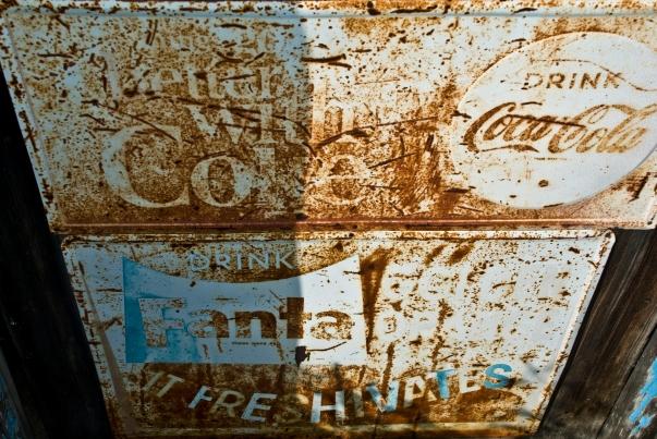 rusted coca-cola and fanta sign