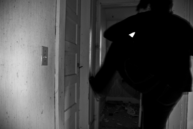 person kicking in door in abandoned house