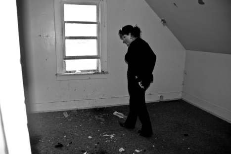 person inside empty room in abandoned house