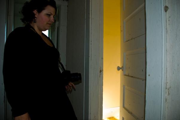person beside half-open door in abandoned house