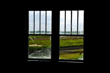 window with broken glass, green fields outside