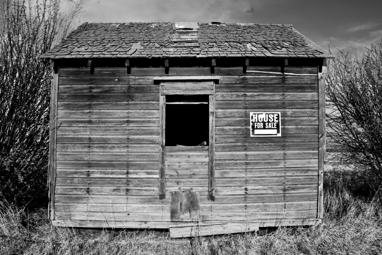 tiny old shack with house for sale sign