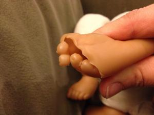 a plastic doll foot with a crack across the toes