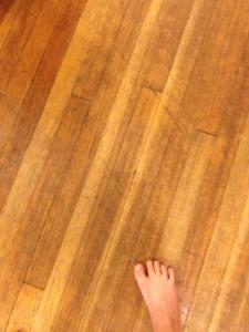 a foot on a scratched wood floor