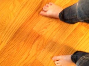 two blurry child's feet on a wooden floor